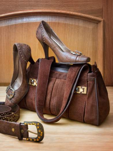 Brown bag, shoes and a belt on wooden background